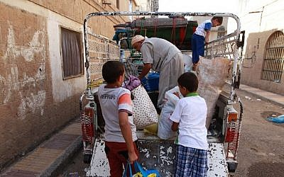 A Yemeni family packs their belongings into the back of a truck in the capital Sanaa as they escape clashes in the city, March 29, 2015. (photo credit: AFP/MOHAMMED HUWAIS)