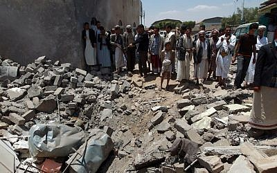 Yemenis gather near the rubble of houses close to Sanaa Airport, March 31, 2015,  after they were destroyed in an air strike a Saudi-led coalition warplanes, .  (AFP/ MOHAMMED HUWAIS)