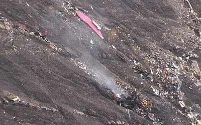A screen grab taken from an AFP TV video on March 24, 2015 shows smoke billowing from scattered debris of the Germanwings Airbus A320 at the crash site in the French Alps above the southeastern town of Seyne. (photo credit: AFP/DENIS BOIS /GRIPMEDIA / AFP TV)