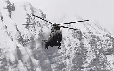 A helicopter flies near Seyne, south-eastern France, on March 25, 2015, near the site where a Germanwings Airbus A320 crashed in the French Alps (Photo credit: Boris Horvat/AFP)