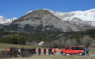 Rescue workers and Red Cross members pay tribute at a memorial for the victims of the Germanwings plane crash in Le Vernet on March 27, 2015. The Germanwings co-pilot who crashed his Airbus into the French Alps, killing all 150 aboard, hid a serious illness from the airline, prosecutors said amid reports he was severely depressed. (photo credit: AFP / BORIS HORVAT)
