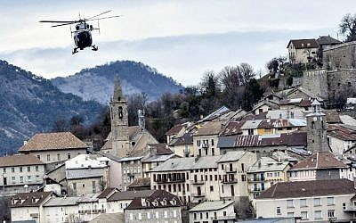 A helicopter of the French gendarmerie flies over Seyne-les-Alpes on March 28, 2015, near the site where a Germanwings flight crashed in the French Alps, killing all 150 aboard. photo credit: AFP/JEFF PACHOUD)