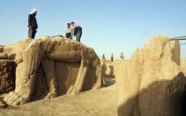 A file picture taken on July 17, 2001 shows Iraqi workers cleaning a statue of winged bull at an archeological site in Nimrud, 35 Kilometers (22 miles) southeast of the northern city of Mosul. The Islamic State group has begun bulldozing the ancient Assyrian city of Nimrud in Iraq, the government said, in the jihadists' latest attack on the country's historical heritage. (photo credit: AFP/Karim SAHIB)