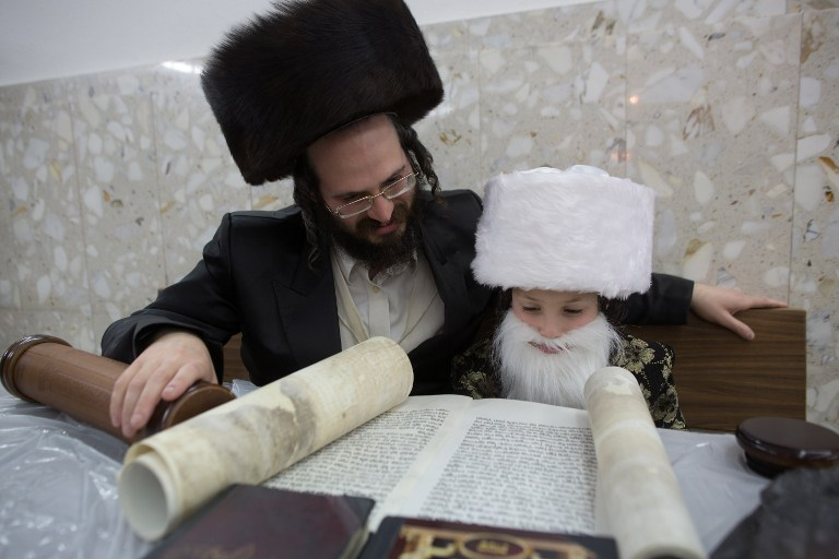 An ultra-Orthodox Jewish man and his dressed-up child read the book of Esther at a synagogue in the Israeli city of Bnei Brak on March 4, 2015.  (photo credit: AFP PHOTO / MENAHEM KAHANA)
