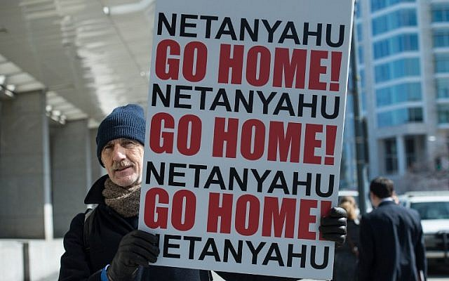 A man holds a sign outside the Washington Convention Center where Israeli Prime Minister Benjamin Netanyahu addressed the American Israel Public Affairs Committee (AIPAC) policy conference in Washington, DC, on March 2, 2015. (AFP/NICHOLAS KAMM)