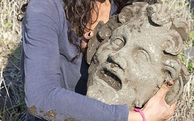 A member of the archaeological team holds the bronze mask of the god Pan, uncovered at the University of Haifa's excavation at Hippos-Sussita. (photo credit: JTA via University of Haifa)