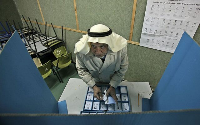 Israeli Arab Abdullah Talash, 74, chooses his ballot in order to vote in Israel's general election at a polling station in the northern Israeli Arab village of Umm Al-Fahm, February 10, 2009 (photo credit: AP/Muhammad Muheissen)