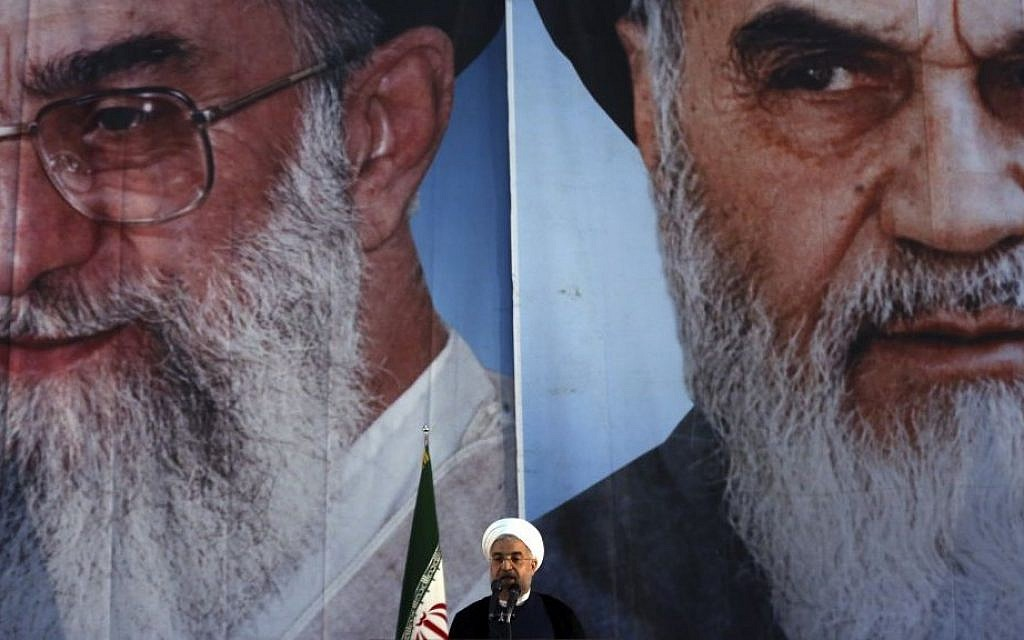 Iranian President Hassan Rouhani makes an address in front of portraits of the supreme leader Ayatollah Ali Khamenei, left, and Ayatollah Khomeini, the founder of the Islamic Republic, during a ceremony marking the 25th anniversary of Khomeini's death, at his shrine just outside Tehran, June 3, 2014. (photo credit: AP Photo/Vahid Salemi)