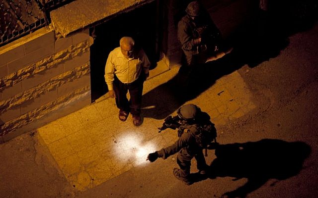 In this Monday, June 16, 2014 file photo, Israeli soldiers arrest Abdel Aziz Dweik, speaker of the long-defunct Palestinian parliament and a senior Hamas figure, at his home during a military operation to search for three missing Israeli teenagers, in the West Bank city of Hebron (photo credit: AP/Majdi Mohammed)