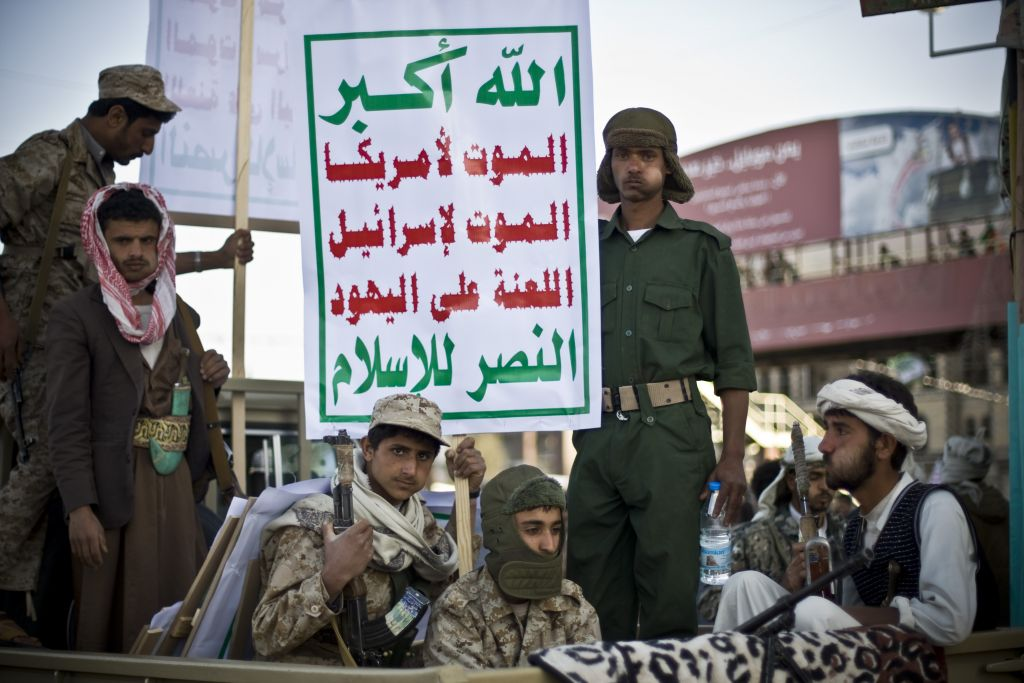 Houthi Shiite fighters wearing army uniforms ride on a pickup truck as they guard a street during a demonstration in Sanaa, Yemen, January 23, 2015. Their sign reads 'death to Israel, cursed be the Jews' (photo credit: AP/Hani Mohammed)