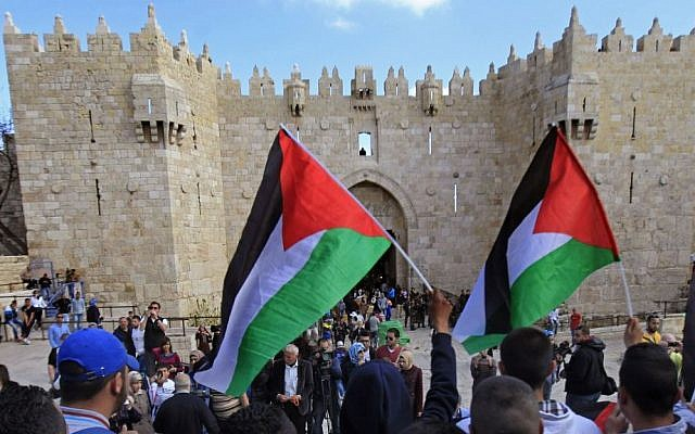 Palestinians carry national flags during a protest marking Land Day in front of the Damascus Gate in Jerusalem's Old City, Monday, March 30, 2015 (photo credit: AP/Mahmoud Illean)