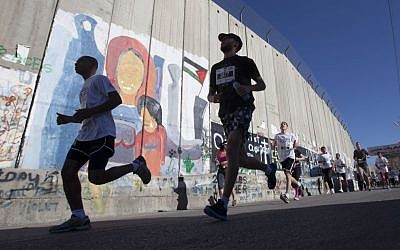 Palestinians and foreigners, including activists, run past the security barrier during the second annual Palestine International Marathon in the West Bank town of Bethlehem, Friday, April 11, 2014 (photo credit: AP/Majdi Mohammed)