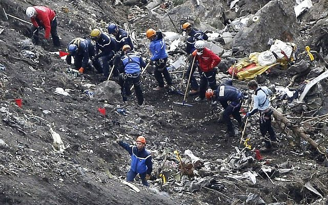 Rescue workers work on debris of the Germanwings jet at the crash site near Seyne-les-Alpes, France, March 26, 2015. (photo credit: AP/Laurent Cipriani)