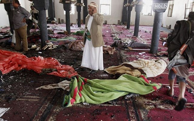 People stand amid bodies covered with blankets in a mosque after a suicide attack during the noon prayer in Sana'a, Yemen, on March 20, 2015. (photo credit: AP/Hani Mohammed)