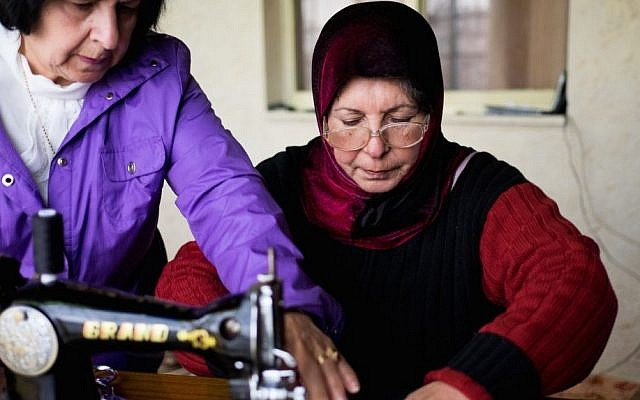Najla shows Om Ahmed how to sew zippers onto pouches photo credit: Shaina Shealy/Times of Israel