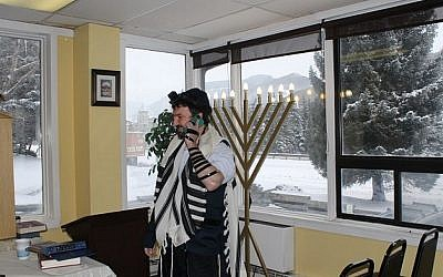 Dovid Mintz, the Chabad rabbi in Vail, Colo., works the phone trying to corral a minyan on a powdery morning at one of North America's most popular ski towns. (Photo credit: Uriel Heilman/JTA)