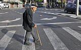 Illustrative: An elderly man crosses the street in Tel Aviv, May 20, 2009. (Serge Attal/Flash90)