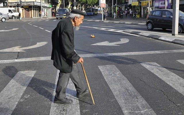 Illustrative: An elderly man crosses the street in Tel Aviv, May 20, 2009. (Serge Attal/Flash90)