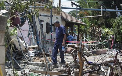 A man inspects the damage to a house following a rocket attack by terrorists from the Gaza Strip on the Israeli town of Yehud, beside Israel's Ben Gurion International Airport, on July 22, 2014. (Photo credit: Yonatan Sindel/Flash90)