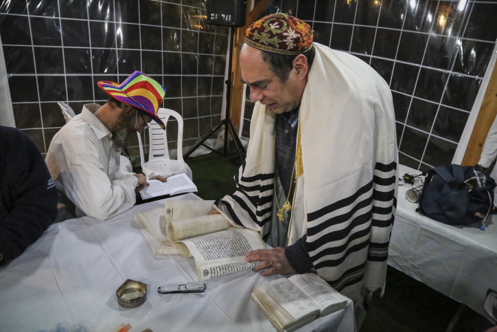 Jews take part in the reading of the Megillat Esther on the eve of the Jewish Purim holiday, at the Oz VeGaon outpost in Gush Etzion. March 4, 2015. (photo credit: Gershon Elinson/Flash90)
