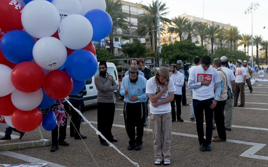 Right wing supporters seen praying before a rally in support of Prime Minister Benjamin Netanyahu, at Rabin Square in Tel Aviv on March 15, 2015. (photo credit: Ben Kelmer/Flash90)