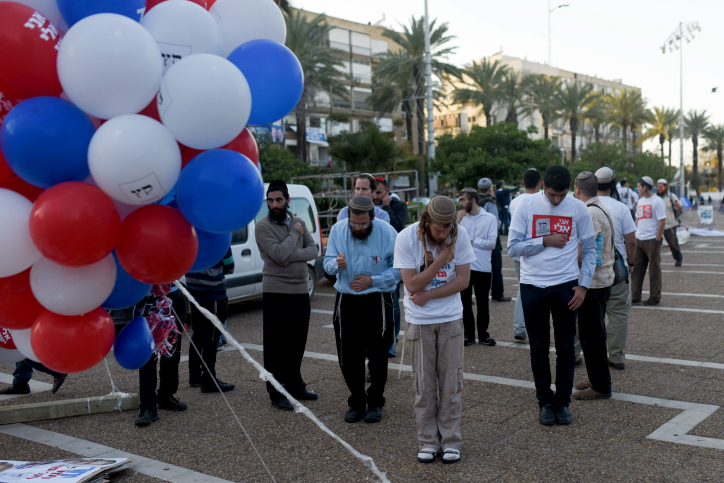 Israelis seen praying before a rally in support of Prime Minister Benjamin Netanyahu, at Rabin Square in Tel Aviv on March 15, 2015. (photo credit: Ben Kelmer/Flash90)
