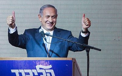Benjamin Netanyahu gives the thumbs-up to supporters at the Likud party headquarters in Tel Aviv, early on March 18, 2015, hours after the TV exit polls were announced for the previous day's elections. (Miriam Alster/Flash90)