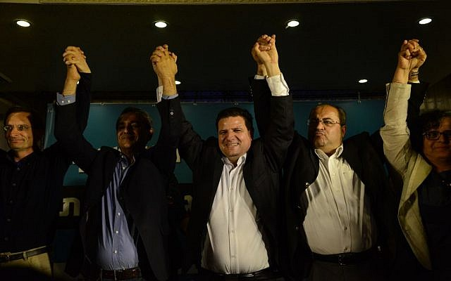 Ayman Odeh (center), head of Israel's Joint (Arab) List, reacts at party headquarters in the northern Israeli town of Nazareth as exit polls in the general elections are announced, March 17, 2015 (photo credit: Basel Awidat/Flash90)