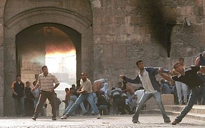 Arab residents of Jerusalem throw rocks at Israeli police near the Lions Gate in Jerusalem's Old City on October 6, 2000, at the outset of the second Palestinian intifada, or uprising (photo credit: Nati Shohat/Flash90)