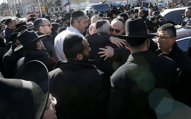Mourners embrace each other after funeral services for the seven siblings killed in a house fire, Sunday, March 22, 2015, in the Brooklyn borough of New York. (photo credit: AP/Julio Cortez)
