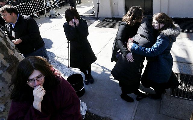 A woman is consoled as others cry as vehicles carrying the remains of the seven siblings killed in a house fire depart after funeral services, Sunday, March 22, 2015, in the Brooklyn borough of New York. (photo credit: AP/Julio Cortez)
