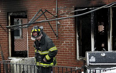 An FDNY firefighter looks over the scene of a house fire Saturday, March 21, 2015, in the Brooklyn borough of New York. (photo credit: AP/Craig Ruttle)