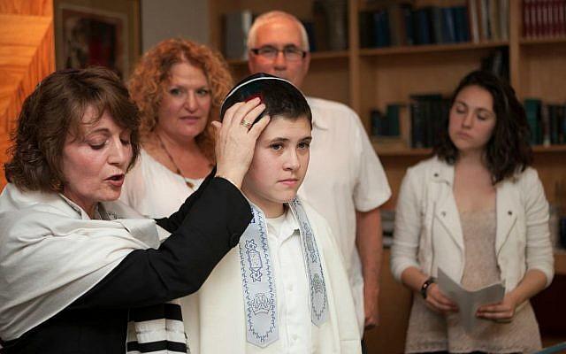 Rabbi Tsipi Gabai blesses Tom Chai Sosnik, a transgender teenage boy, as his parents and sister look on at Tehiyah Day School, El Cerrito, California, March 13. 2015. (Misha Bruk, BrukStudios.com)