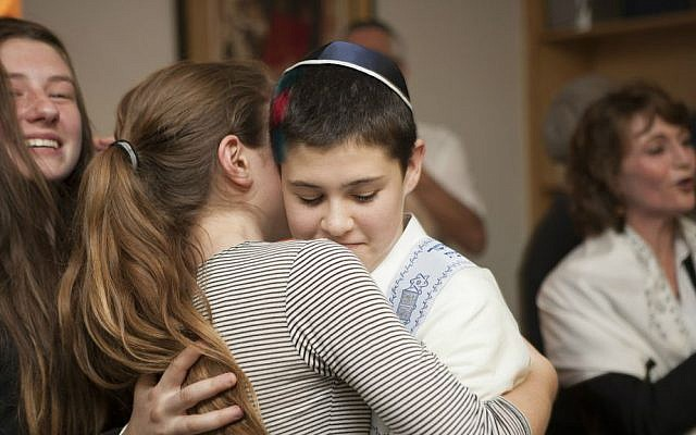 Tom Chai Sosnik is hugged by a classmate following ceremony at Tehiyah Day School marking his transitioning from female to male, March 13, 2015.(photo credit: Misha Bruk, BrukStudios.com)