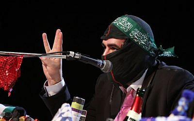 In this Saturday, March 7, 2015 photo Deniz Yucel of German newspaper 'taz' wears a mask during the 'Hate Poetry' show in the Theaterlabor in Bielefeld, Germany. (AP Photo/Oliver Krato)