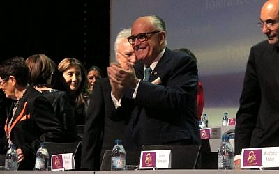 Former New York City Mayor Rudy Giuliani claps his hands at the start of a day-long conference on human rights organized by the Iranian exile opposition group National Council of Resistance of Iran on Saturday, March 7, 2015. Giuliani was one of the main speakers. (photo credit: AP Photo/Frank Jordans)