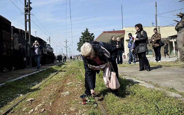 A woman places flowers on a rail at the old train station of the Greek northern town of Thessaloniki, on Sunday, March 15, 2015. Residents of this northern Greek city on Sunday marked the 72nd anniversary of the roundup and deportation of its Jews to Nazi extermination camps during World War II. (AP Photo/Giannis Papanikos)