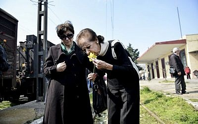 Mina Beneroubi, a survivor of the Holocaust, right, places flowers on rails at the old train station of Thessaloniki, in the Greek northern town of Thessaloniki, on Sunday, March 15, 2015 (AP Photo/Giannis Papanikos)