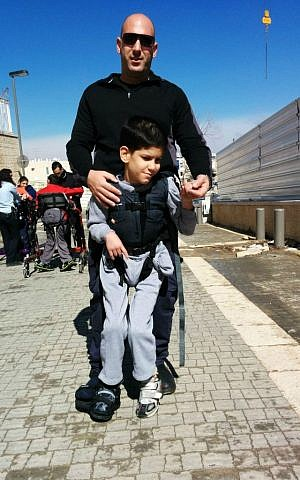 A police officer trains for the Jerusalem Marathon with an ALEH resident using an Upsee harness. (Courtesy of ALEH Jerusalem)
