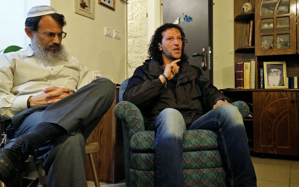 Palestinian nonviolence activist Ali Abu Awwad (right) addresses an Israeli audience at the home of Rabbi Hanan Schlesinger (left) in the settlement of Alon Shvut on Wednesday, February 25, 2015 (photo credit: Elie Leshem/Times of Israel)