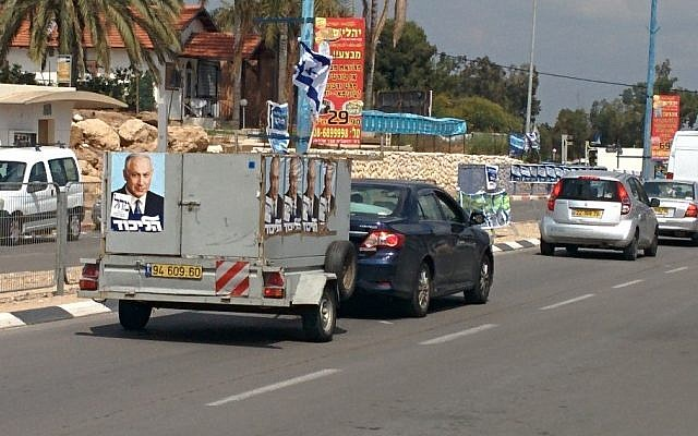 A truck with placards bearing the image of Likud party leader Prime Minister Benjamin Netanyahu drives down a street in the southern city of Sderot (photo credit: Ilan Ben Zion/Times of Israel)
