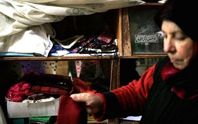 Om Ahmed and her embroidery collection (photo credit: Shaina Shealy/Times of Israel)