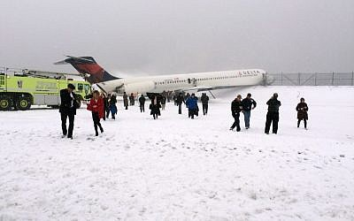 In this photo provided by Amber Reid, a passenger on Delta Flight 1086, passengers leave the plane after the aircraft skidded off the runway while landing at LaGuardia Airport in New York City, March 5, 2015. (photo credit: AP/Amber Reid)