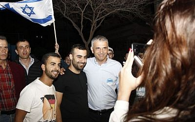 Moshe Kahlon, the Kulanu party leader, takes photographs with supporters before the polls close in South Tel Aviv on Mar. 17, 2015. (Photo credit: Judah Ari Gross/Times of Israel)