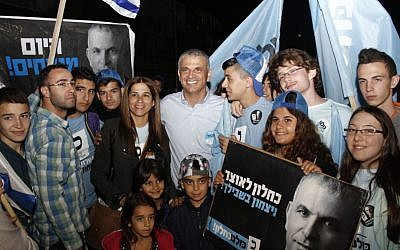 Moshe Kahlon poses with volunteers of his Kulanu party in South Tel Aviv on Mar. 17, 2015. Kahlon traveled up and down Israel's coast, rallying support before the polls close. (photo credit: Judah Ari Gross/Times of Israel)