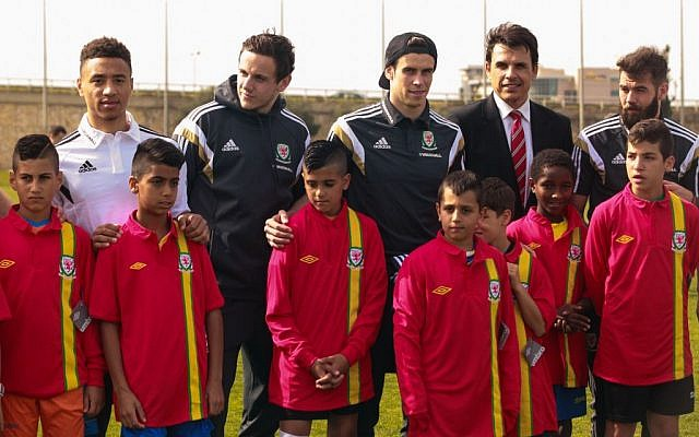 Welsh Football Team plays coexistence football with Jewish and Arab children from northern communities in Israel. The children were handed Welsh football team shirts by the players and manager Chris Coleman. R-L: Joe Ledley, Chris Coleman and Gareth Bale. (photo credit: Kobi Wolf/Courtesy)