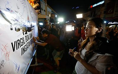 Kelly Wen, wife of a Chinese passenger aboard the missing Malaysia Airlines flight MH370 looks at an MAS airplane poster during an event to mark the one-year anniversary of the plane's disappearance, in Kuala Lumpur, Malaysia, on Friday, March 6, 2015. (AP/Vincent Thian)