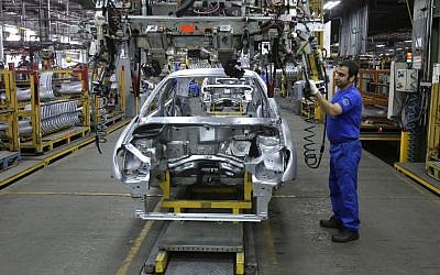 An Iranian worker assembles a car at the Iran Khodro automobile manufacturing plant, just outside Tehran, Iran,  January 18, 2014. (photo credit: AP/Vahid Salemi, File)