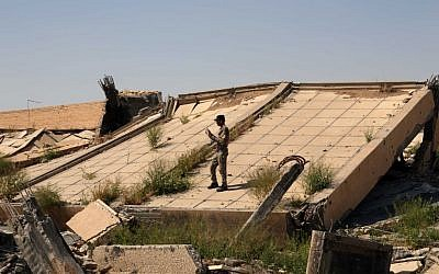 An Iraqi soldier takes photos of the demolished tomb of former Iraqi president, Saddam Hussein, in Tikrit, 130 kilometers (80 miles) north of Baghdad, Iraq, Sunday, March 15, 2015. (photo credit: AP/Khalid Mohammed)