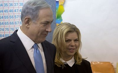 Prime Minister Benjamin Netanyahu stands with his wife Sara after voting in Israel's parliamentary elections in Jerusalem, Tuesday, Mar. 17, 2015. (photo credit: AP Photo/Sebastian Scheiner, Pool)